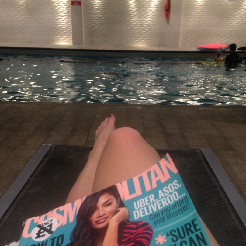 Sitting Poolside with a magazine